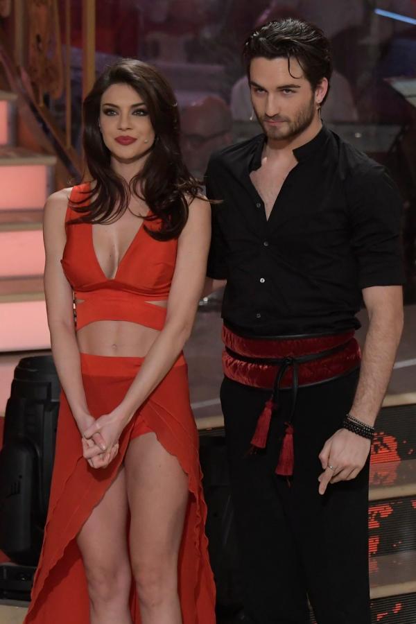 Cristina Ich, într-o fustă roșie și un sutien de aceeași culoar eși partenerul său, Luca Favilla, într-o cămașă neagră