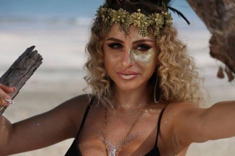 Irina Stroia pe platoul de filmare al emisiunii Insula Iubirii, imbracata intr-un costum de baie negru si are parul cret