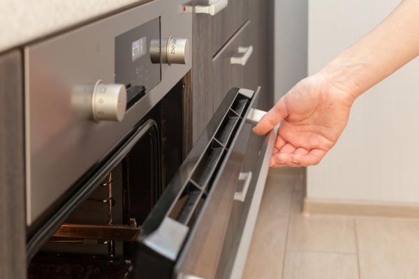 Imagine ilustrativă cu un aragaz deschis de o persoană aflată într-o bucătărie
