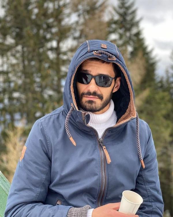 George Burcea, la munte, imbracat cu o geaca albastra si bluza alba
