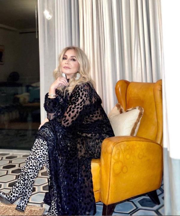 Anastasia Soare imbracata intr-o rochie neagra si cizme animal print
