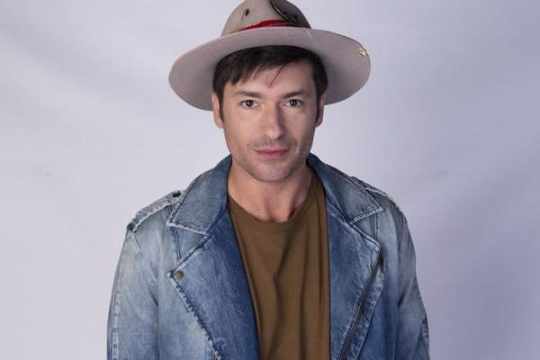 Radu Vâlcan, purtând o pălărie, o geacă de blugi și un tricou maro