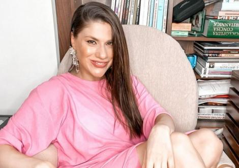 Tily Niculae îmbrăcată într-o rochie roz, largă, are părul pe o parte și stă pe fotoliu