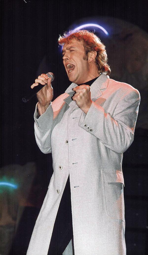 Gabriel Cotabiță, în tinerețe, pe scenă, într-un palton bej