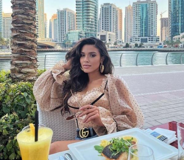 Karmen in Dubai, intr-o bluza crem si pantaloni scurti. Tine un pahar in mana si se afla la o masa