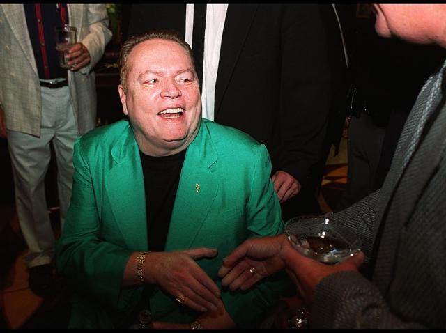 Larry Flynt, în scaunul său cu rotile, purtând un sacou verde