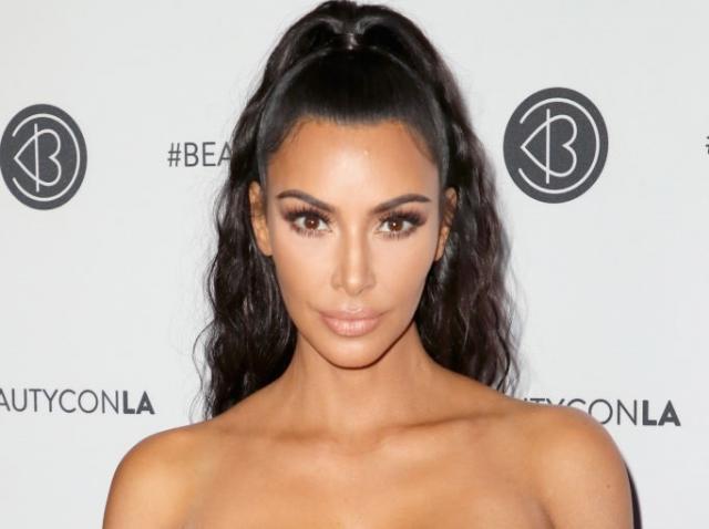 Kim Kardashian imbracata intr-o rochie neagra, cu un decolteu amplu și cu umerii la vedere