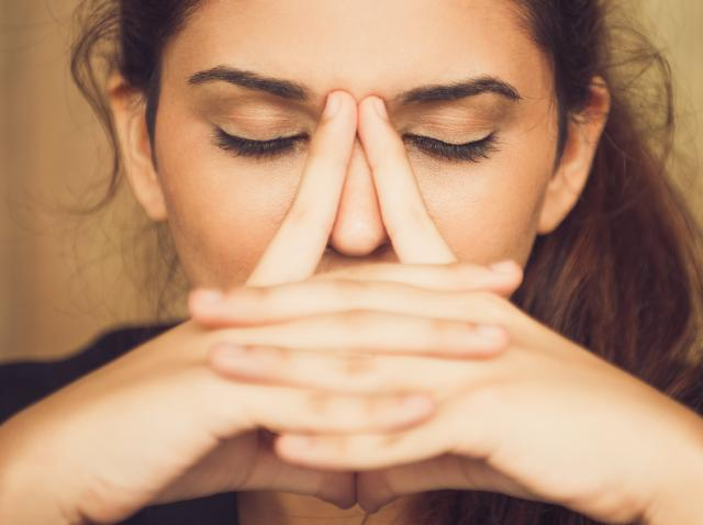 femeie care isi tine nasul, fundal bej