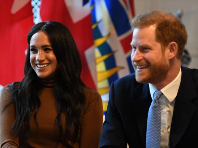 Meghan Markle, într-un pulover maro, alături de Prințui Harry, îmbrăcat la costum