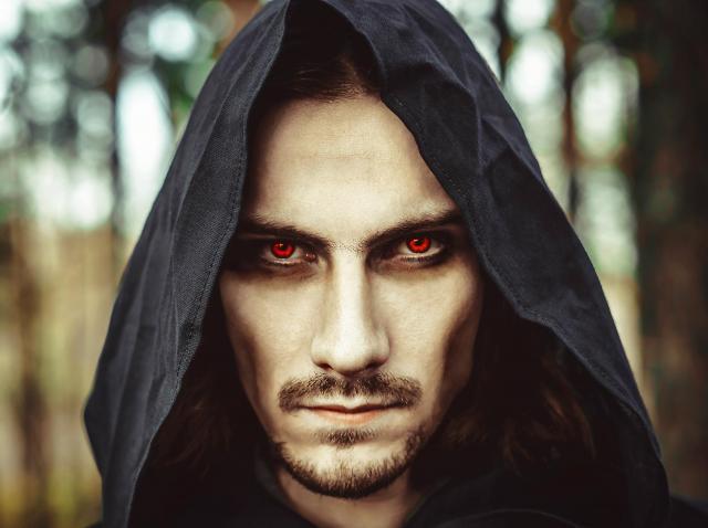 tip vampir, ochi rosii, gluga neagra, padure pe fundal