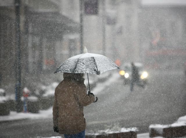 Persoană ținându-și umbrela în mijlocul ninsorii