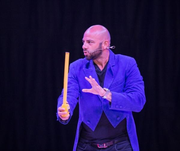 Giani Kiriță intr-un sacou albastru pe scena circului Bellucci și tine o ruleta in mana