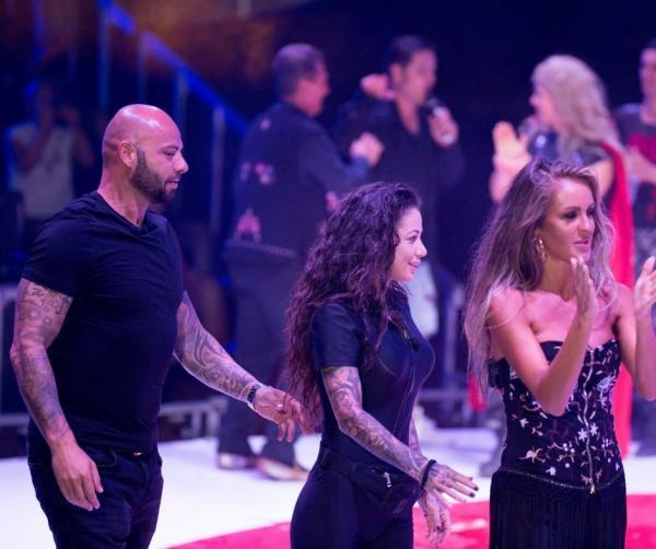 Giani Kiriță intr-un tricou negru pe scena circului Bellucci și tine o ruleta in mana, alaturi de Roxana Vancea si Diana Munteanu
