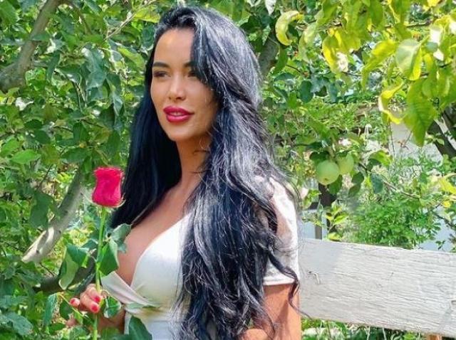 Daniela Crudu intr-o rochie albă si cu un trandafir rosu in mana