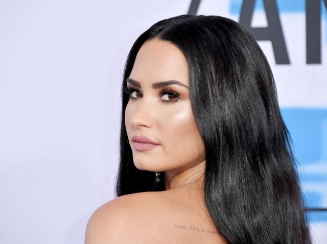 Demi Lovato, portret, cu un umăr gol și părul lung, brunet