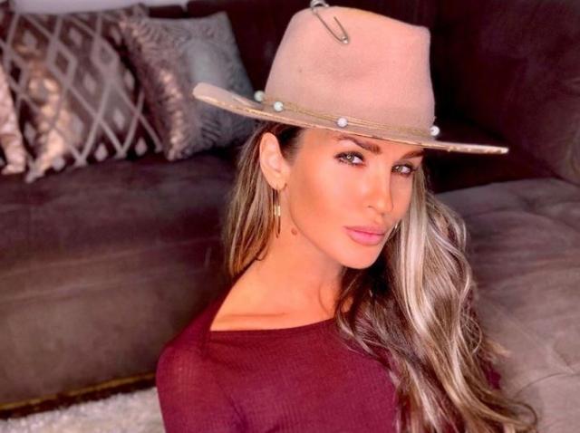 Diana Munteanu cu o pălărie pe cap, imbracata intr-o rochie visinie