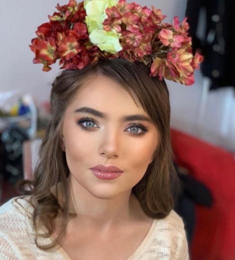 Veronica Stegaru intr-o bluza alba si cu o coronita de flori pe cap