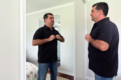 Imagine ilustrativă cu un bărbat îmbrăcându-se în fața unei oglinzi