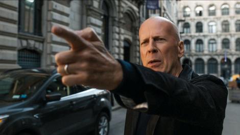 Bruce Willis, Death Wish, imbracat in negru, strada, degetul scos