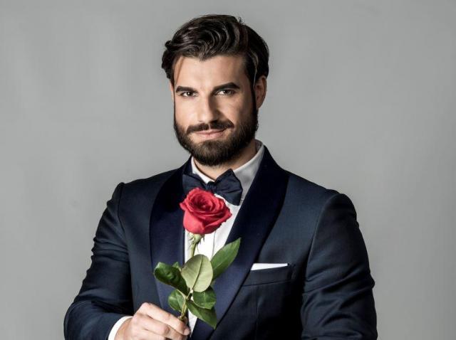 """Andi Constantin de la """"Burlacul"""", îmbrăcat la costum și având un trandafir în mâini"""