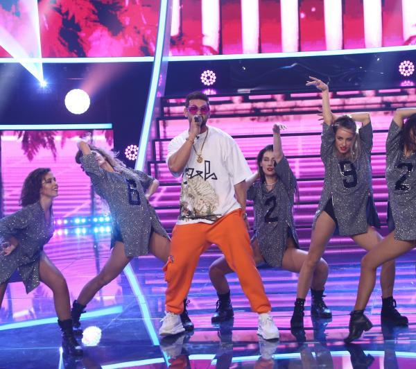 Dorian Popa cu panatloni portocalii și tricou alb