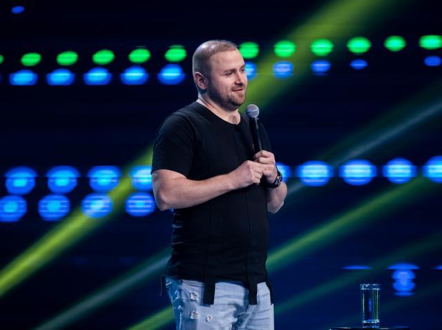 Nae Nicolae intr-un tricou negru și blugi pe scena iUmor