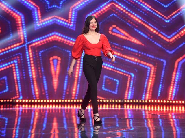 Ionela Irimescu intr-o bluza rosie si pantaloni negri, pe scena iUmor