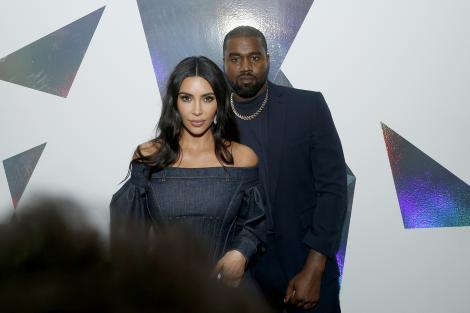 kim kardashian si kanye west imbracati in negru pe covorul rosu al unui eveniment