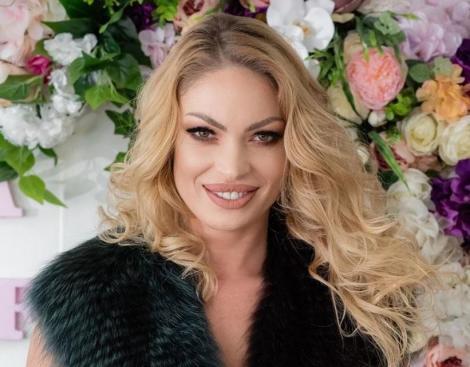Valentina Pelinel intr-o vesta de blană neagra, zambeste și are părul creț
