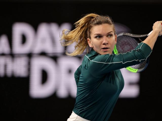 Simona Halep intr-o bluza verde si cu paleta de tenis in mana