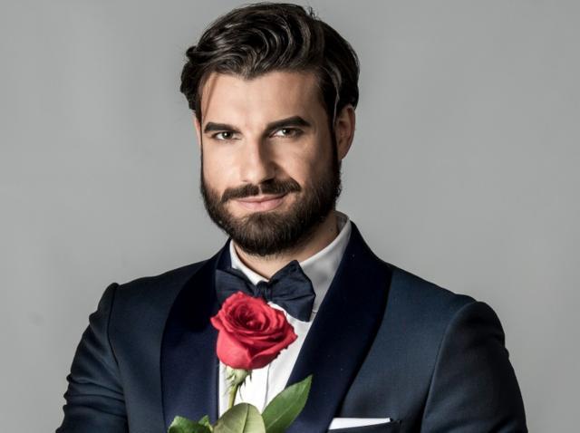 Andi Constantin, purtând sacou, cămașă și papion, ținând un trandafir în mână