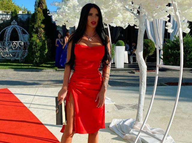 Daniela Crudu intr-o rochie roșie și decoltată, cu o geantă în mână