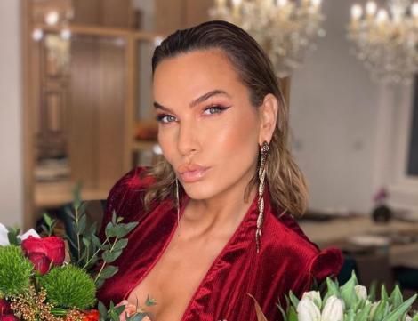 Anna Lesko într-o rochie roșie și ține flori în brațe