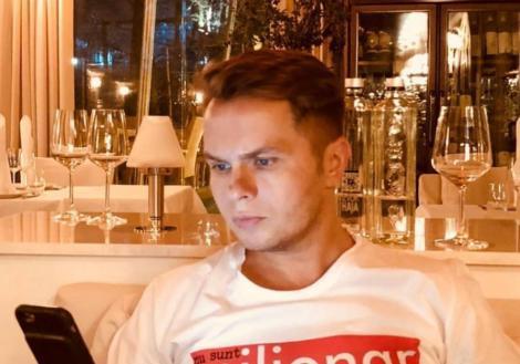 Codin Maticiuc într-un tricou alb și cu telefonul în mână