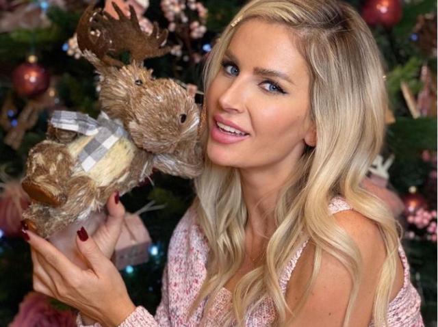 Andreea Bănică într-o bluză roz pal, cu umerii goi și cu un ren n mână