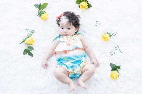 mayah, fetita cu piebaldism, pe pat, cu jucarii in jur, si imbracata intr-un costum simpatic