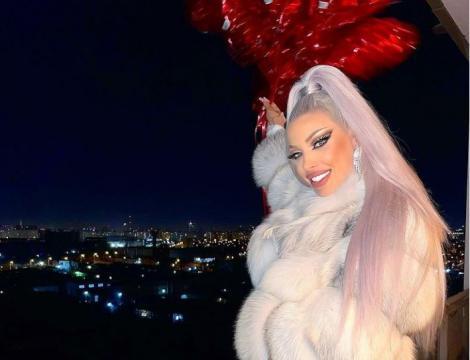Loredana Chivu într-o haină din blană albă și ține în mână câteva baloane