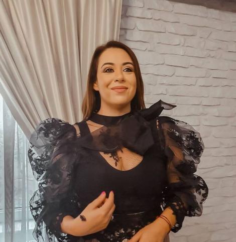 Oana Roman înt-o bluză neagră, din dantelă și cu fundiță la gât
