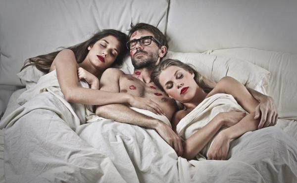 cuplu cu 3 persoane in pat, blonda, bruneta, el brunet cu cohelari, asternut alb