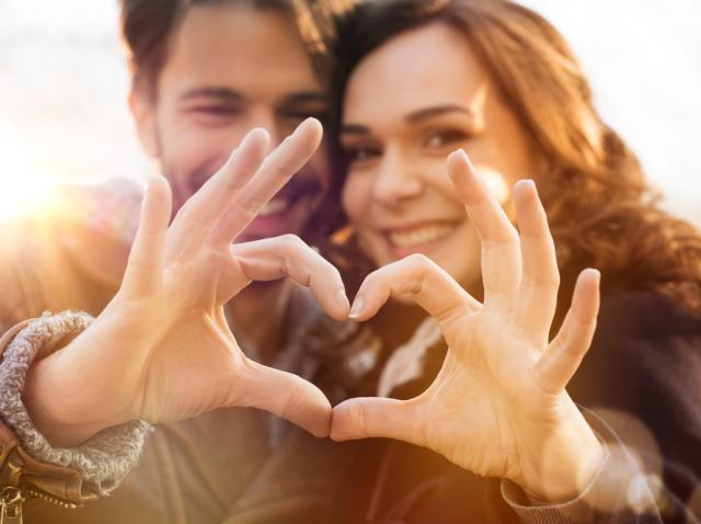 Cuplu care formează o inimioară cu degetele