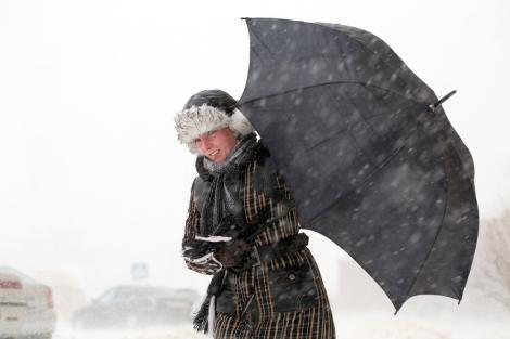 Persoană ținându-și umbrela luată de vânt