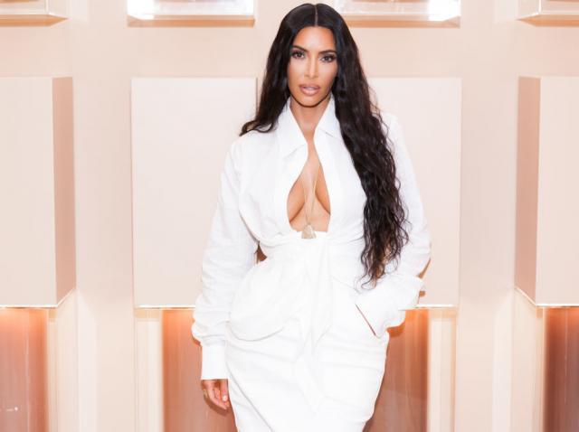 Kim Kardashian imbracata intr-o rochie alba, mulata si cu decolteul la vedere