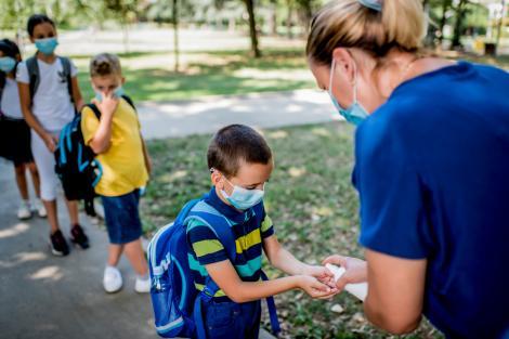 Copiii care isi asteapta randul sa fie dezinfectati pe maini de catre profesoară