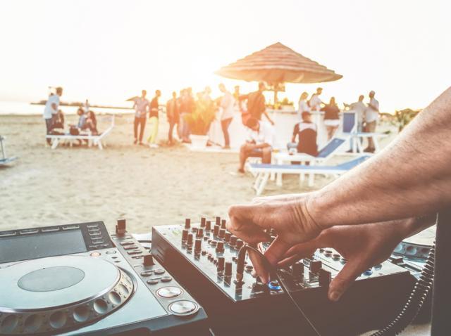 Un DJ, care pune muzică, iar pe plaja oameni care petrec
