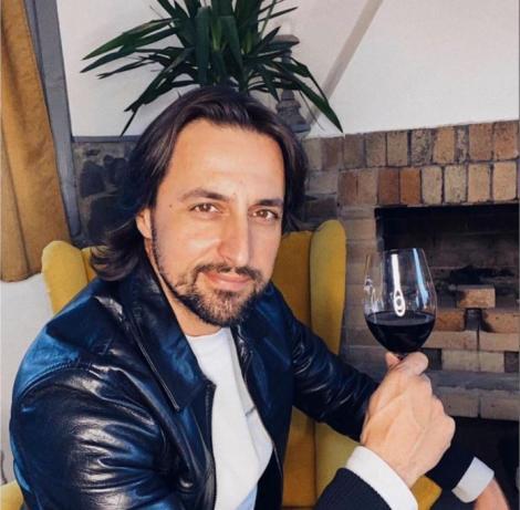 Denis Ștefan imracat intr-o geaca de piele si o bluza alba, tine in mana un pahar cu vin, iar in spate are o planta verde