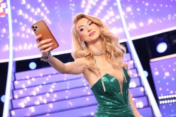 Andreea Bălan pe platoul de filmare al emisiunii Te cunosc de undeva, imbracata intr-o rochie verde și cu telefonul in mana