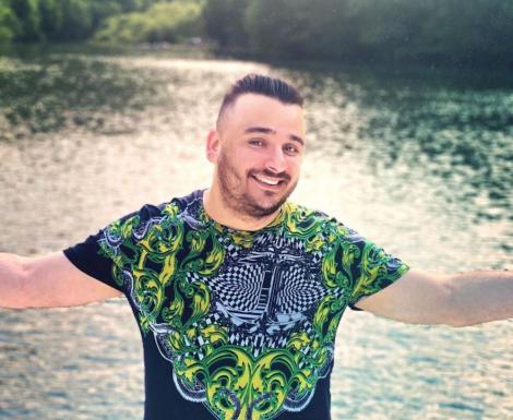 Liviu Guță într-un tricou colorat și o apă în spate