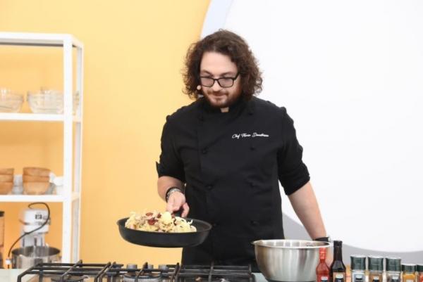 Florin Dumitrescu, în bucătăria Chefi la cuțite, ținând o tigaie în mână