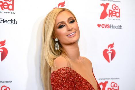 Paris Hilton, purtând o rochie roșie, pe covorul roșu