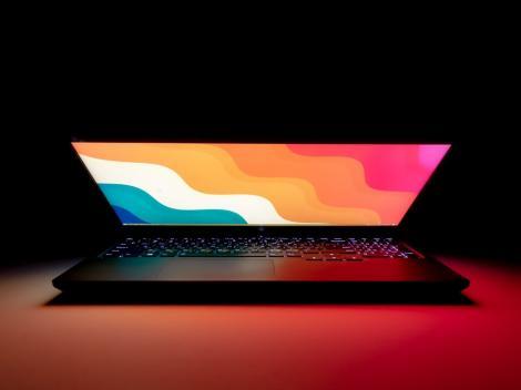 Un laptop pe o masă, cu ecranul aproape deschis